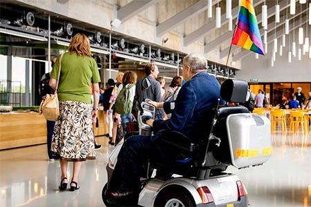 Een bejaarde man met een lhbti-vlaggetje op zijn scootmobiel (Foto: ANP)